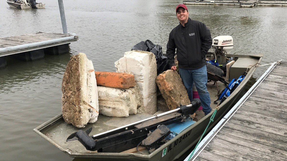 A student stands on a boat with trash he removed from the lake.